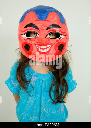 young girl wearing Chinese Paper Mache mask - Stock Image