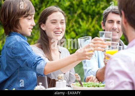 Family clinking glasses at outdoor gathering - Stock-Bilder
