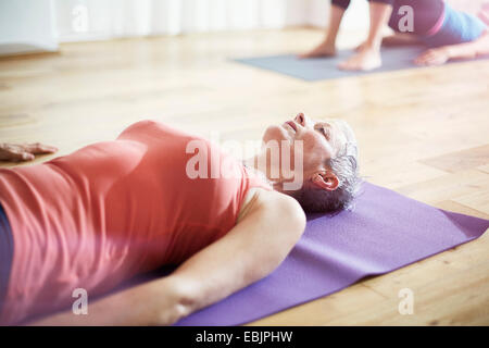 Mature woman lying on back in pilates class - Stock Image