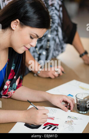 Young seamstress painting fashion design on work table - Stock Image