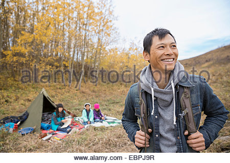 Smiling man camping with family - Stock Image