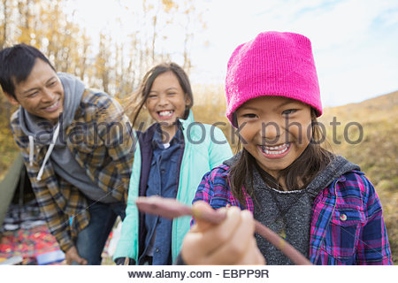 Girl holding snake at campsite - Stock Image