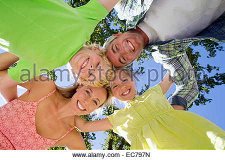 Portrait of a family in a group huddle - Stock-Bilder