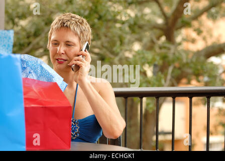 Mature woman talking on a mobile cell phone at a table with brightly colored shopping bags. - Stock Image