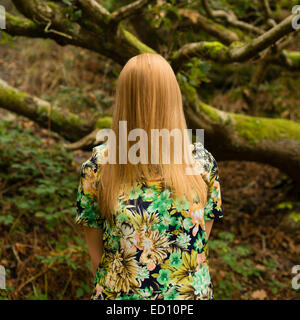 Shyness: An enigmatic image of a  young woman girl with long blonde hair hiding obscuring  covering her entire face - Stock Image
