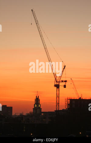 London, UK. 29 December, 2014. London skyline seen at sunset on the last Monday of 2014. A crane towers St Anne's - Stock Image