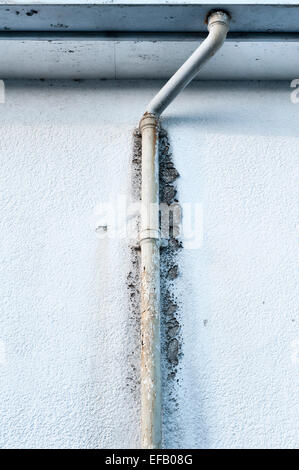 An old corroded cast-iron drainpipe, blocked and overflowing, causing damage to a rendered wall - Stock Image