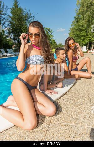 Beautiful woman in bikini posing on the edge of the swimming pool behind her friends - Stock-Bilder