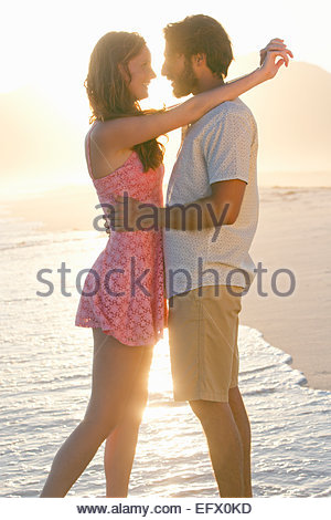 Romantic couple embracing, about to kiss, on sunny beach - Stock-Bilder