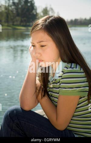 Sad, depressed teen Vietnamese/Caucasian girl outside. MR  © Myrleen Pearson - Stock-Bilder