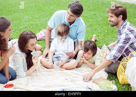 Family playing card game at picnic - Stock-Bilder