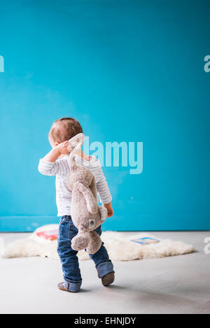 Toddler walking away from camera with rabbit toy over shoulder - Stock Image