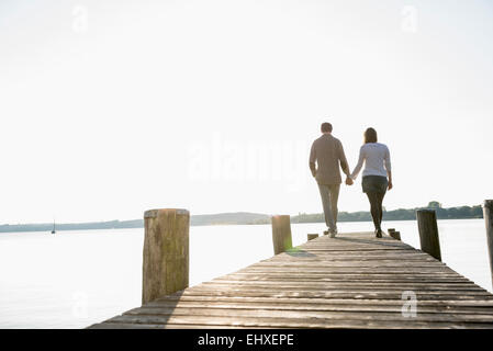 Couple walking on wooden jetty sunset - Stock Image