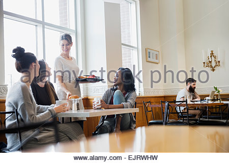 Woman serving friends at cafe table - Stock-Bilder