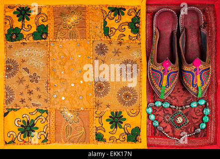 Colorful ethnic shoes, necklace and yellow Rajasthan cushion cover on flea market in India - Stock-Bilder