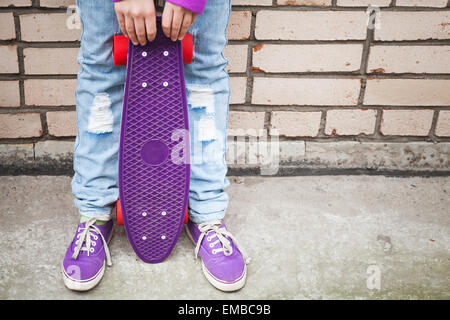 Teenage girl in jeans and gumshoes holds skateboard near by gray urban brick wall - Stock-Bilder