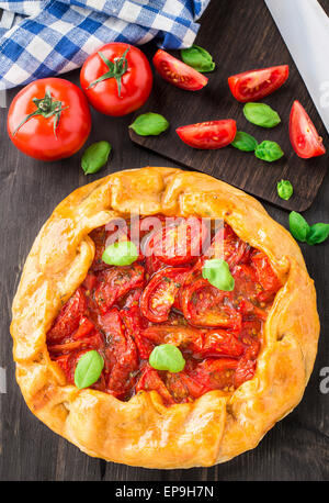 Galette with tomato and basil on a table - Stock Image
