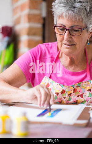 Senior woman painting an abstract picture - Stock-Bilder
