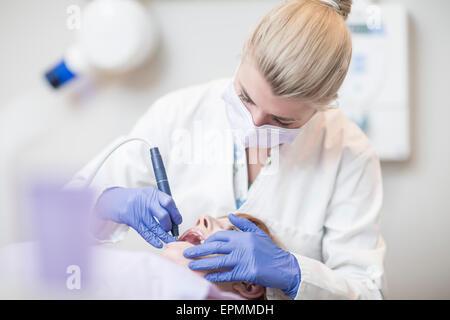 Dentist using amalgam carrier - Stock Image