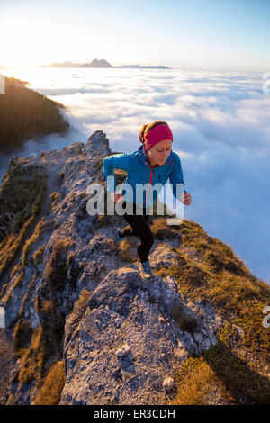 Young woman running above the clouds, Salzburg, Austria - Stock Image
