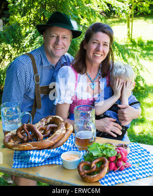 bavarian family sitting outside on a bench and smiling - Stock-Bilder
