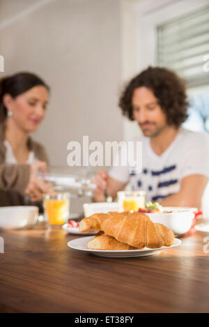 Croissants on dining table and mid adult couple having breakfast in the background, Munich, Bavaria, Germany - Stock-Bilder