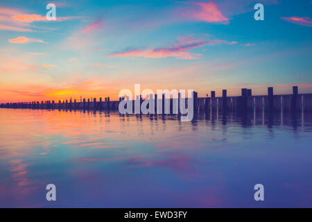Beautiful ocean scene with wooden pier at sunset - Stock Image