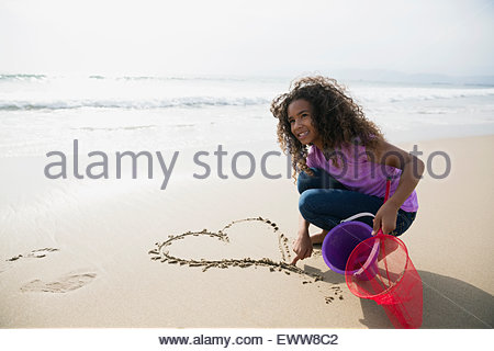 Girl drawing heart-shape in sand on beach - Stock-Bilder