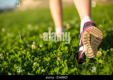Hiker walking in the green grass outdoors, low angle close up of the foot. - Stock-Bilder