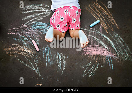 Overhead view of girl lying on ground drawing with chalk - Stock-Bilder