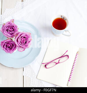 three pink roses in vases on blue plate with mug of tea and open notebook with glasses and pencil - Stock Image