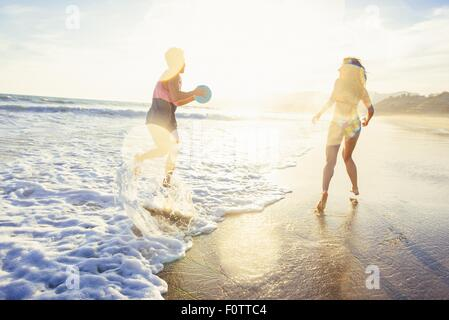Young couple fooling around on beach, on sea, sunset - Stock Image