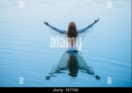 Rear view of young woman standing in blue lake with arms open - Stock Image