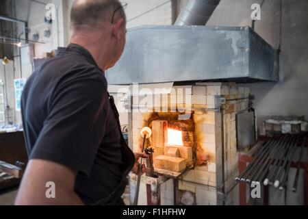 Glassblower drawing molten glass from furnace - Stock-Bilder