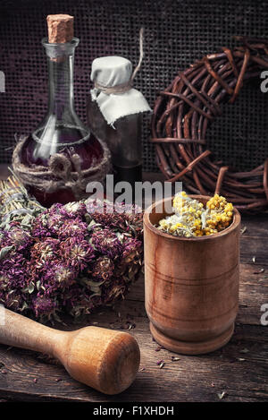 Cut  bunch medicinal plants,mortar on wooden table.Toned. - Stock Image
