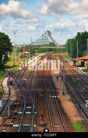 Threads of rails towards the center of Riga on the background of the building of the Latvian National Library and - Stock Image