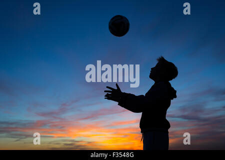 silhouette of a boy playing outside at dusk - Stock-Bilder