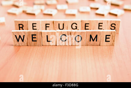 Refugees Welcome text on wooden tiles letters - Stock Image