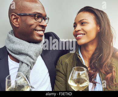 Romantic young African American couple sitting arm in arm enjoying glasses of white wine and smiling lovingly into - Stock-Bilder