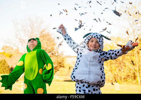 Two boys in costume catching and throwing leaves - Stock Image