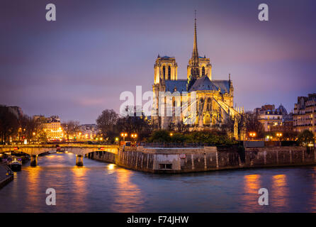 Illuminated Cathedral of Notre Dame on Ile de La Cite with the Archbishop's Bridge and Seine River, Paris, France. - Stock Image