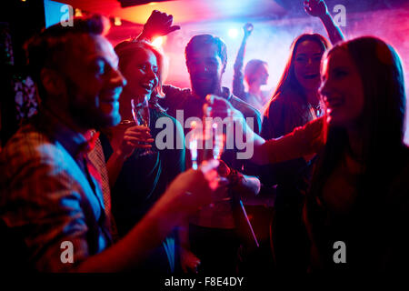 Group of young people celebrating with drinks in nightclub - Stock Image