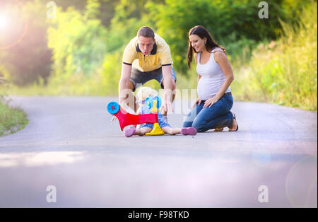 Little girl fallen of her bike, her parents helping her to stand up - Stock Image