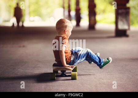 Cute little boy with his skateboard on a walk in the city - Stock Image
