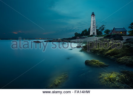 A moonlit white lighthouse and a small red house by the rocks at the New Haven shore or beach at night. The blue - Stock Image