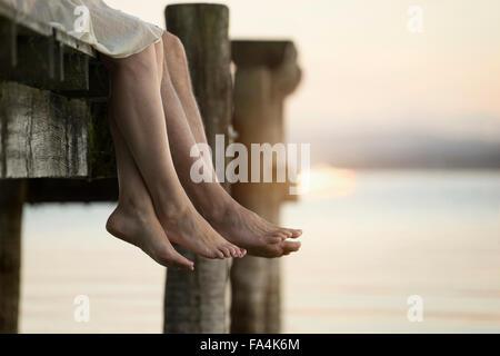 Couple legs dangling on pier, Bavaria, Germany - Stock-Bilder