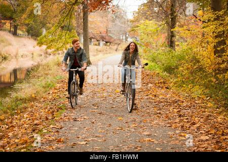 Happy young couple cycling on riverside in autumn - Stock Image