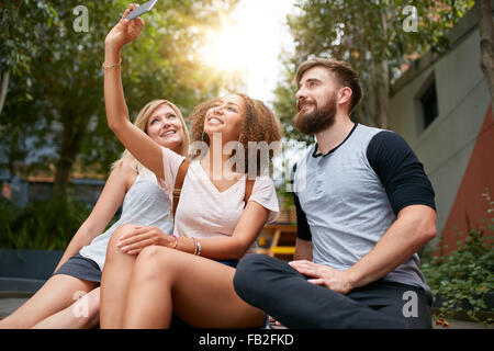 Three young friends taking a selfie with cellphone. Multiracial group of young people having fun together while - Stock Image