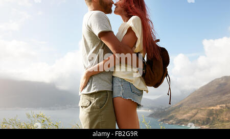 Cropped shot of young man and woman standing close to each other face to face. Romantic couple embracing outdoors. - Stock-Bilder