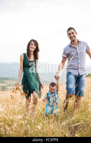Smiling Parents Walking With Young Son in Field - Stock-Bilder